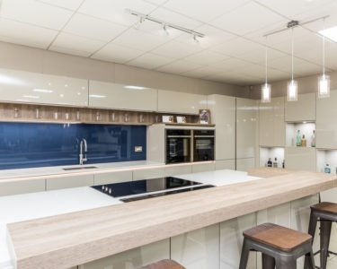 Rotpunkt Modern high gloss white kitchen with blue glass backsplash