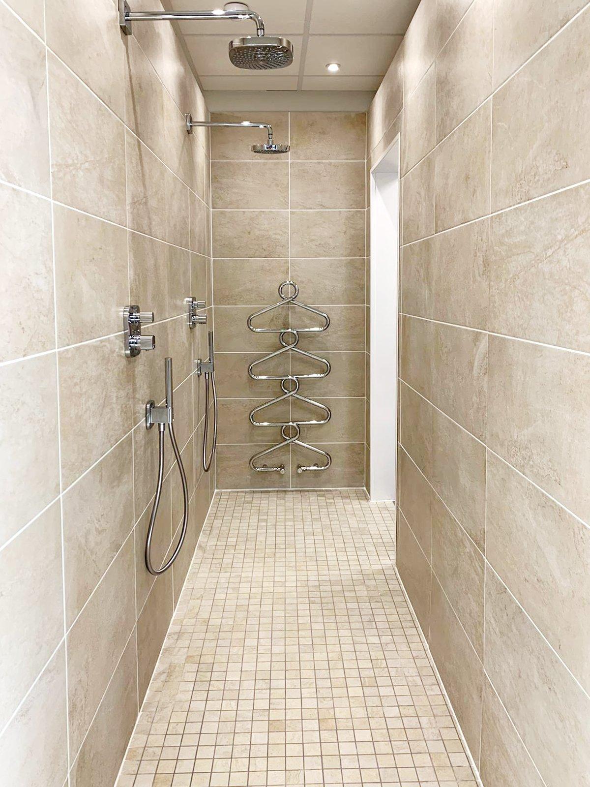 Walk-in twin shower heads in enclosed wet room area of a modern bathroom