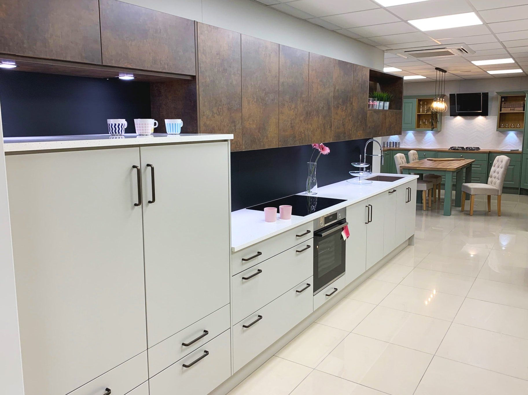 (foreground) Rotpunkt matt kitchen with copper effect units (background) Sheraton Shaker traditional kitchen in Green