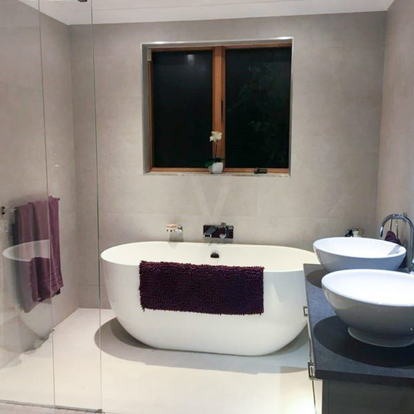 modern bathroom with freestanding bath with rounded edges and statement basins