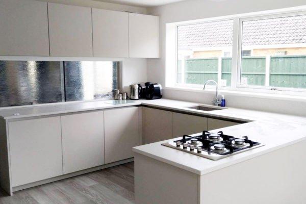 white kitchen with statement steel splashback