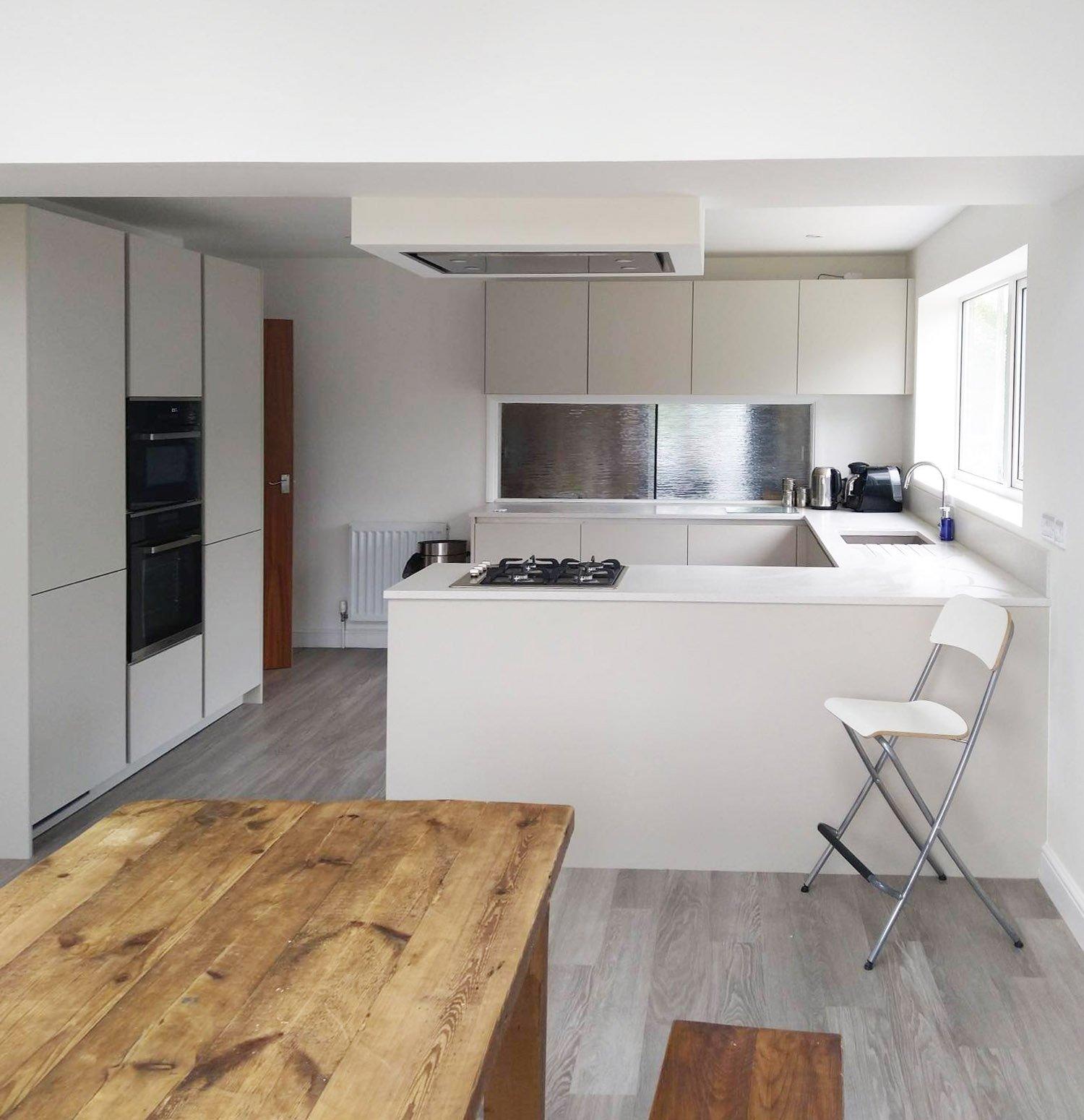 white kitchen with steel splashback
